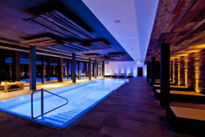 beleuchteter indoor pool bei nacht im armona medical hotel in thiersee