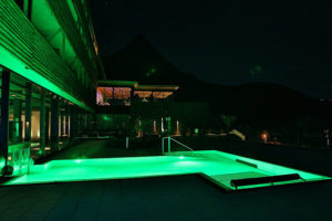 beleuchteter outdoor pool bei nacht im armona medical hotel in thiersee